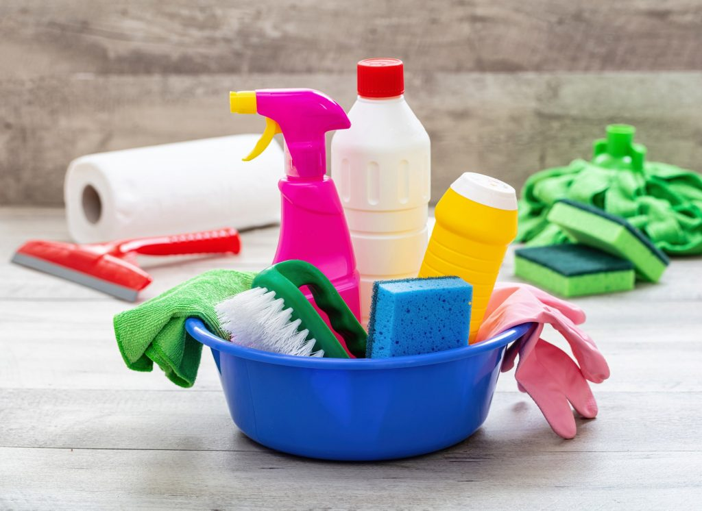 Cleaning supplies in a blue bowl, wooden floor background.