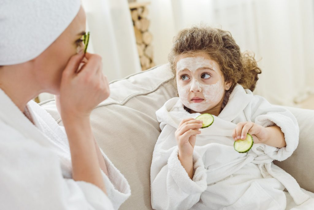 mother and daughter with cucumber slices doing facial mask