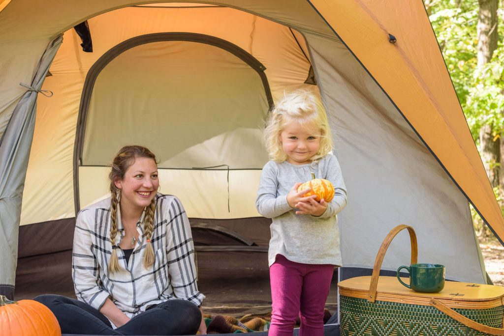 Young mom with little girl camping out in autumn